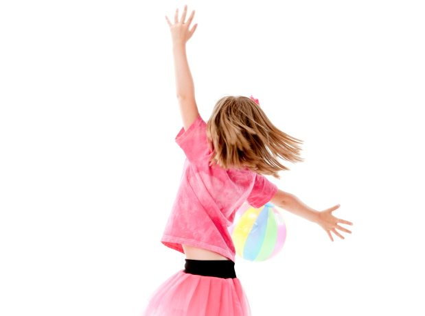 A full length image of a caucasian little girl playing with a beach ball.